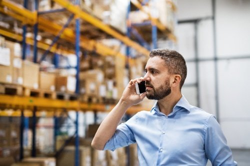 Deskless worker in a warehouse talking to coworkers on his mobile phone