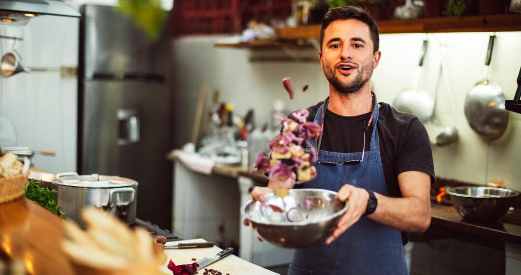Restaurant employee tossing salad