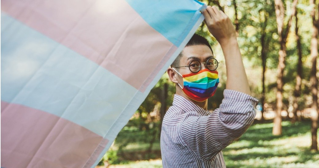 Person with rainbow mask and Transgender Pride flag