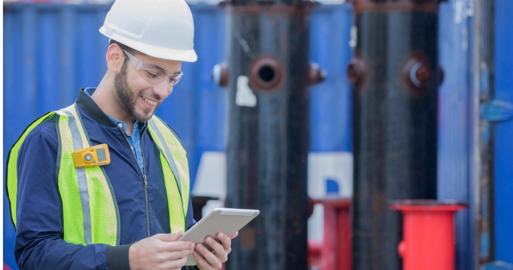 Engaged engineer reading internal communications updates on a tablet